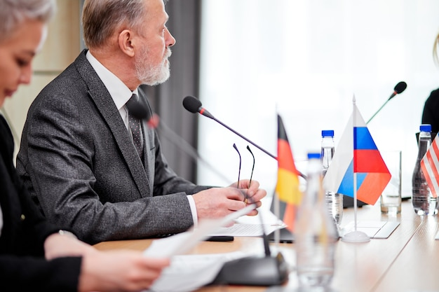 Un gruppo di persone esecutive europee che discutono del piano per il futuro in un moderno edificio per uffici, indossando abiti formali, si siedono insieme usando il microfono per dare il discorso