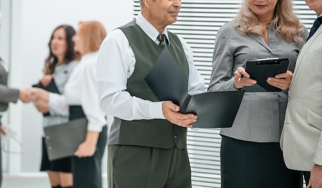 Gruppo di dipendenti esperti in piedi nell'ufficio della banca