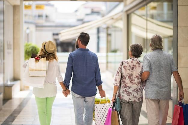 Gruppo o famiglia che cammina insieme in un centro commerciale facendo shopping e tenendo in mano le borse della spesa - adulti e anziani che guardano i negozi o i negozi