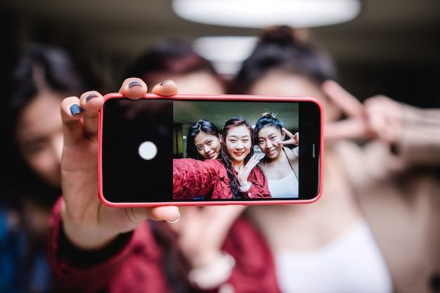 Gruppo di amiche che prendono un selfie insieme a un concetto di amicizia del telefono cellulare