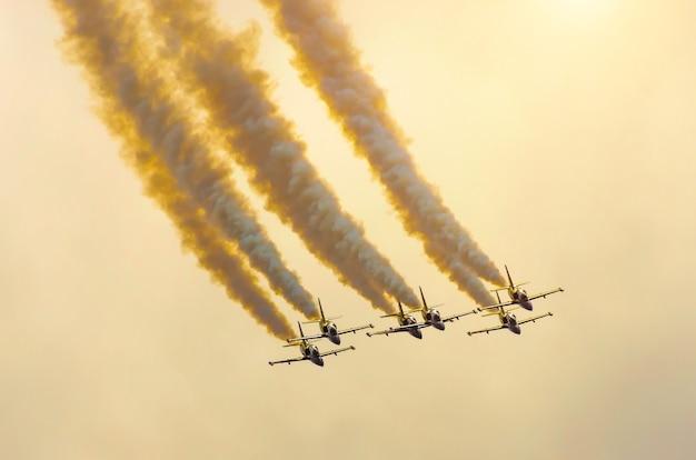Un gruppo di aerei da combattimento vola con una traccia di fumo contro un cielo arancione con nuvole.