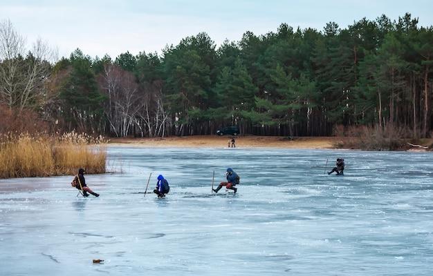 Gruppo di pescatori in inverno che pescano sul fiume
