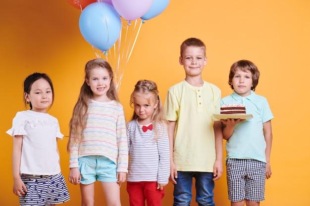 Un gruppo di cinque bambini di compleanno carino in abbigliamento casual in piedi contro il muro giallo durante la celebrazione