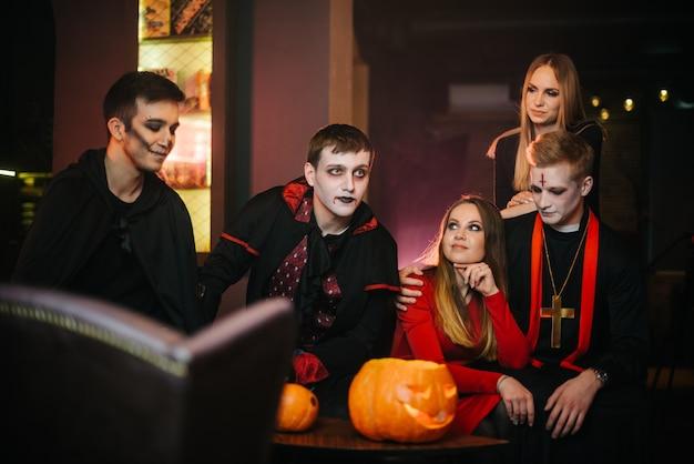 Un gruppo di cinque amici sta festeggiando halloween in un caffè. ragazzi vestiti da spaventosi mostri natalizi e vestiti con costumi colorati. zucca intagliata natalizia sul tavolo