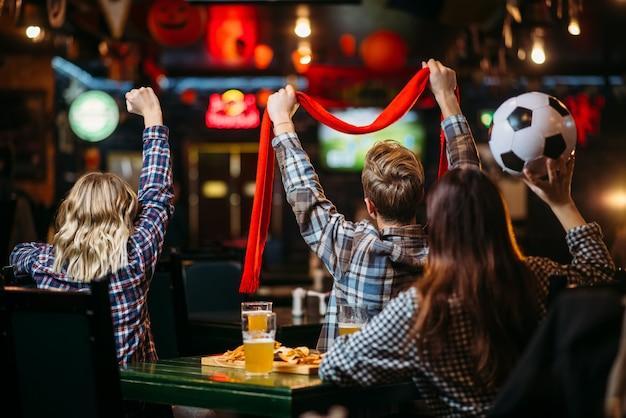 Gruppo di tifosi di calcio guardando la partita nel bar dello sport