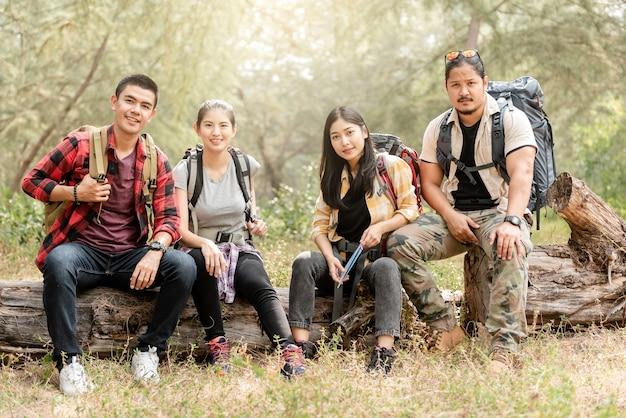 Un gruppo di quattro viaggiatori con zaino e sacco a pelo maschii e femminili asiatici che si siedono su un albero nella foresta che osserva in su