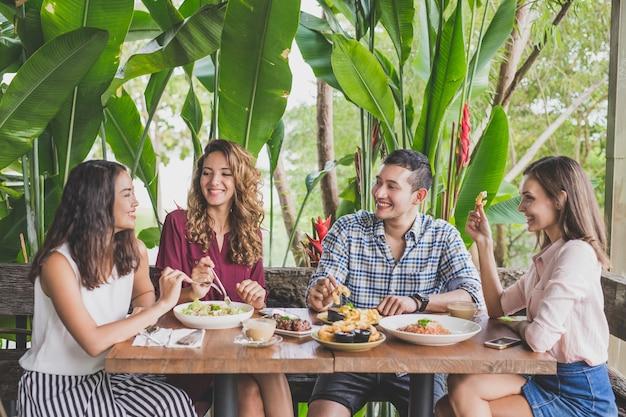Gruppo di quattro migliori amici che hanno conversazione divertente durante il pranzo insieme in un bar
