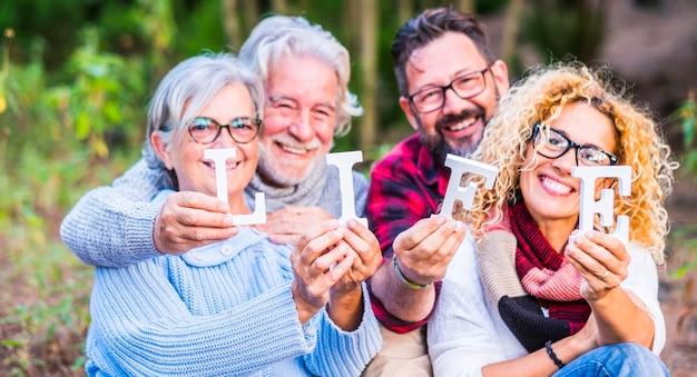 Gruppo di quattro persone caucasiche famiglia insieme a blocchi di vita in posa felice e allegra - backgroud sfocato della foresta naturale all'aperto - salva il pianeta e goditi lo stile di vita oncept