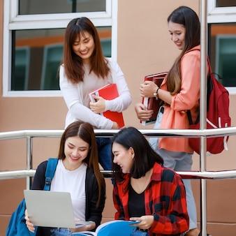 Un gruppo di quattro ragazze dello studente di college che tengono i libri e il computer portatile che si siedono e che parlano.