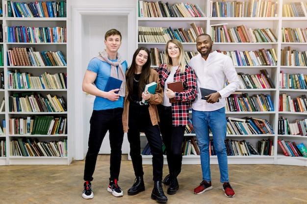 Gruppo di quattro studenti multietnici sorridenti fiduciosi, ragazze e ragazzi in abbigliamento casual, in posa in biblioteca, in possesso di libri e guardando camer