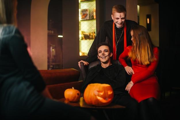 Un gruppo di quattro amici sta festeggiando halloween in un caffè. ragazzi vestiti da spaventosi mostri natalizi. zucca intagliata sul tavolo.