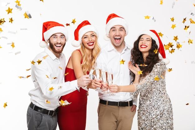 Un gruppo di quattro amici vestiti elegantemente felici che stanno sotto la doccia dei coriandoli isolata sopra bianco
