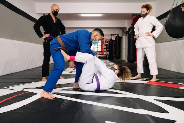 Gruppo di quattro partner di arti marziali e un istruttore che praticano nuove tecniche con maschere facciali a causa del covid19 su un tappetino da palestra