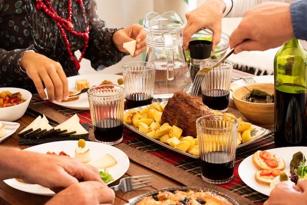 Gruppo di quattro persone che mangiano e bevono insieme a casa - celebrando qualcosa con pollo e vino - mani che prendono il cibo dal centro del tavolo