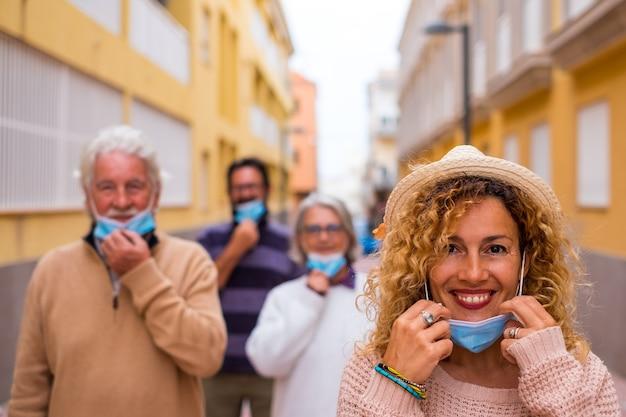 Gruppo di quattro persone che rispettano la distanza sociale all'aperto che si tolgono la maschera medica e chirurgica dopo il covid 19 e la quarantena - libertà e ritorno allo stile di vita del concetto di normalità
