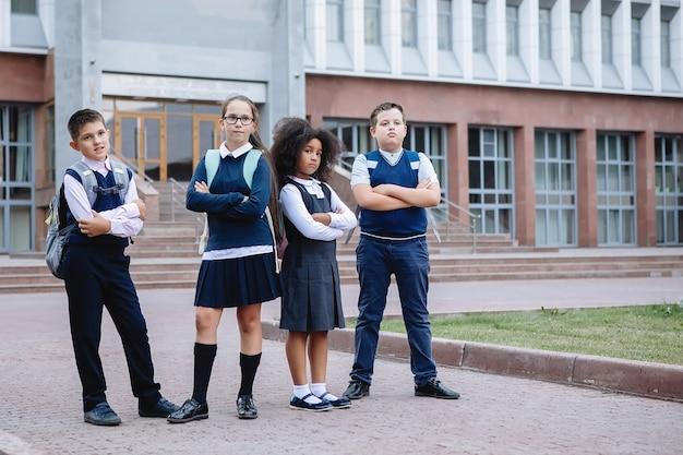 Gruppo quattro adolescenti scolari in uniforme sono in piedi davanti alla scuola, in posa per la telecamera.