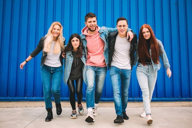 Un gruppo di quattro giovani amici diversi in abito di jeans sembrano spensierati, giovani e felici camminando per le strade della città. moda di abiti urbani, libertà, amicizia, concetto di stile.