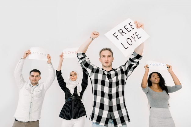 Gruppo di quattro giovani multietnici che sollevano manifesti di fogli di carta per i diritti lgbt, amore gratuito, fiducia e felicità