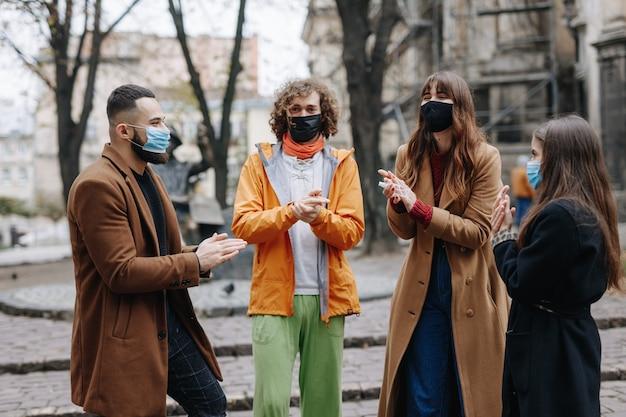 Gruppo di quattro giovani che usano disinfettanti e indossano maschere mediche mentre si incontrano durante il coronavirus. concetto di prevenzione e protezione.