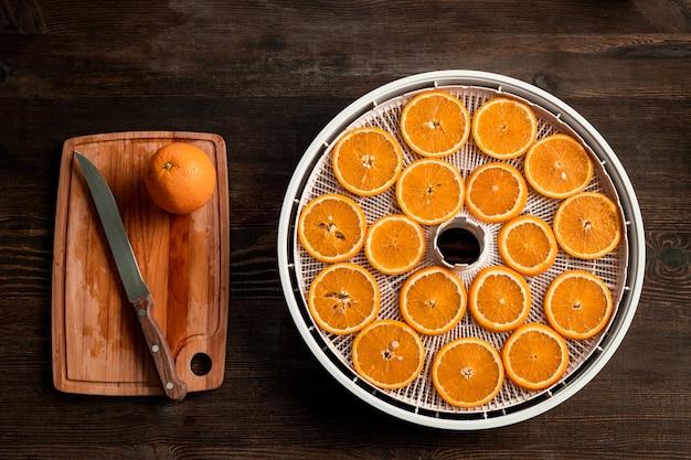 Gruppo di fette d'arancia fresche e metà dei frutti sul tagliere di legno sul tavolo da cucina tagliato dalla casalinga per mangiare