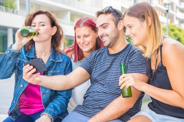 Gruppo di amici che bevono una birra e guardano il telefono Foto Premium