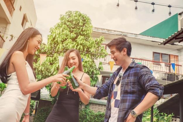 Gruppo amici giovani asiatici che celebrano festival della birra felici mentre vi godete la festa a casa