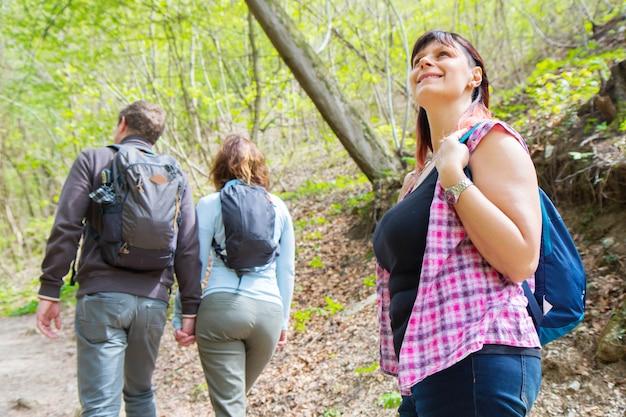 Gruppo di amici stanno facendo un'escursione nella foresta