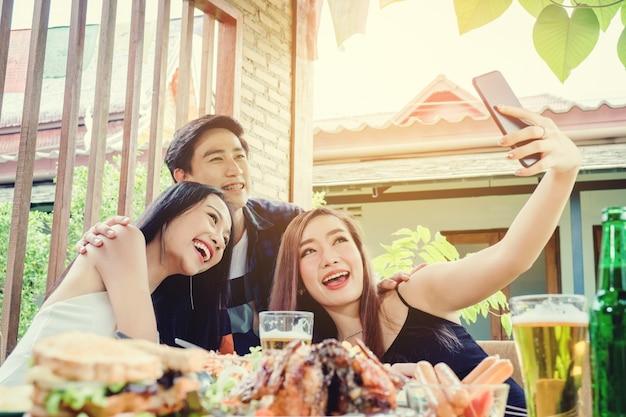 Il gruppo di amici sta prendendo il selfie e sta mangiando il cibo sta godendo felice nel paese