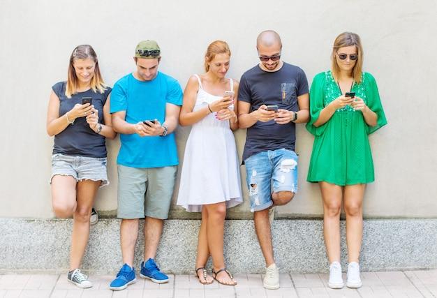 Un gruppo di amici sta guardando il telefono cellulare intelligente Foto Premium