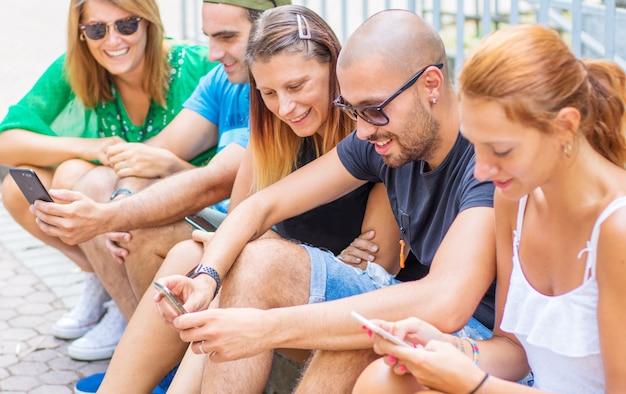 Il gruppo di amici sta guardando il telefono cellulare intelligente