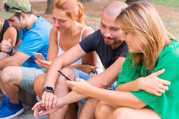 Il gruppo di amici sta guardando il telefono cellulare intelligente Foto Premium