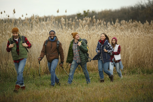 Gruppo di amici in campeggio o in escursione in una giornata autunnale. uomini e donne con zaini turistici che attraversano la foresta, parlano, ridono. attività di svago, amicizia, fine settimana.