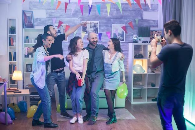 Gruppo di amici che celebrano la loro amicizia a una festa e scattano una foto di gruppo.