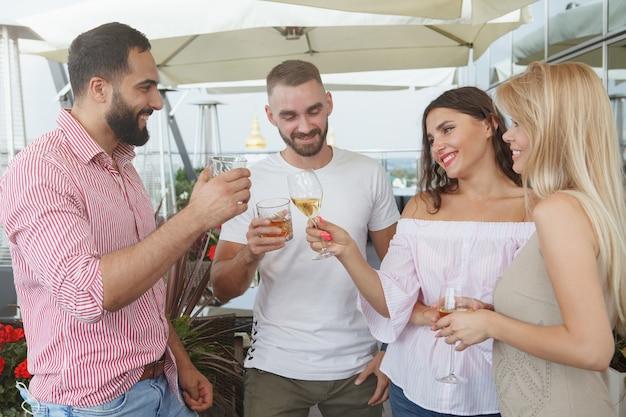 Gruppo di amici che chiacchierano con gioia, bevendo un drink al bar sul tetto