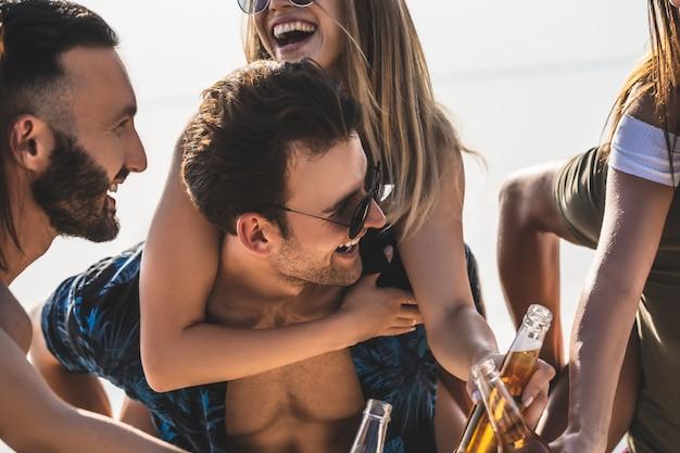 Il gruppo di amici tintinna le bottiglie all'aperto