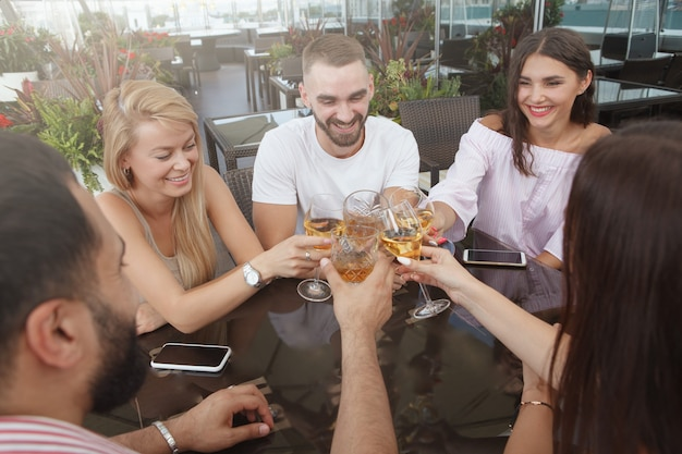 Gruppo di amici tintinnio di bicchieri, bevendo al ristorante sul tetto