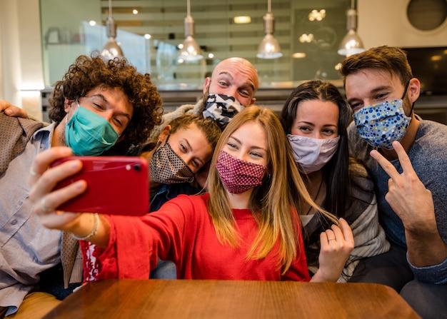 Gruppo di amici coperti da maschera facciale al ristorante