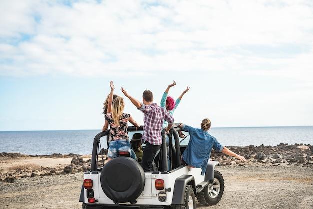 Gruppo di amici che fanno un'escursione nel deserto con un'auto 4x4 convertibile - amicizia, tour, gioventù, stile di vita e concetto di vacanza - focus sui corpi di ragazzi