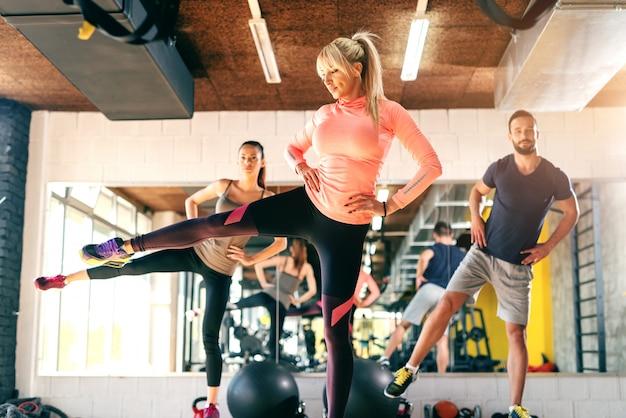 Il gruppo di amici che fanno la forma fisica si esercita per le gambe in palestra. sullo sfondo il loro riflesso speculare.