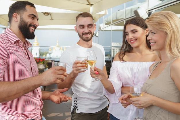 Gruppo di amici che bevono su una festa sul tetto