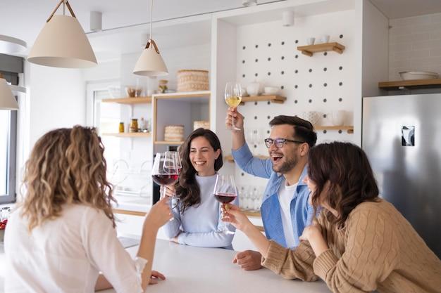 Gruppo di amici che bevono vino in cucina