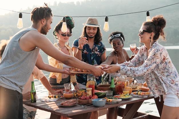 Gruppo di amici che mangiano hot dog durante il pranzo all'aria aperta