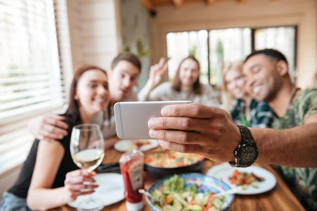 Gruppo di amici che mangiano e che prendono selfie al tavolo