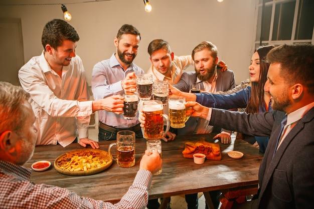 Gruppo di amici che si godono un drink serale con birra su un tavolo di legno