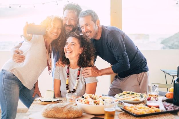 Un gruppo di amici si diverte insieme durante un pranzo all'aperto nella terrazza di casa e si fa un moderno selfie con lo smartphone da condividere sugli account dei social media per la vita su internet