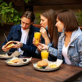 Gruppo di amici che mangiano hamburger con patatine fritte e succo di frutta
