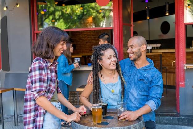 Un gruppo di amici che bevono e si divertono fuori in un pub.