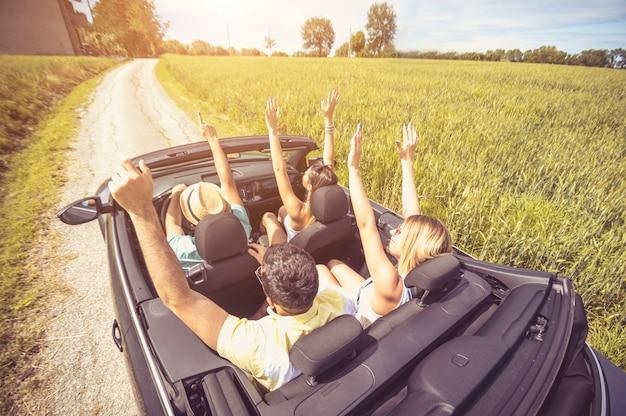 Gruppo di amici divertendosi in viaggio in macchina
