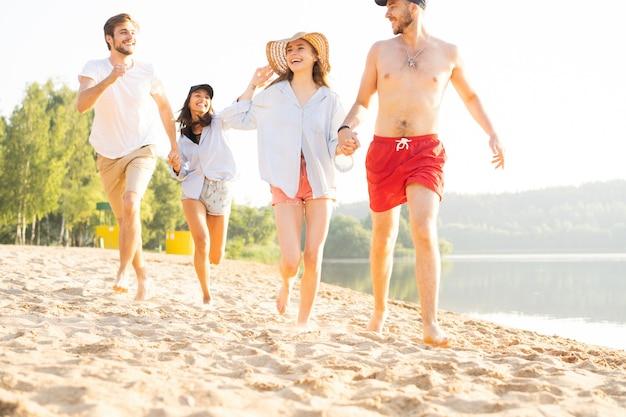Gruppo di amici divertendosi correndo lungo la spiaggia