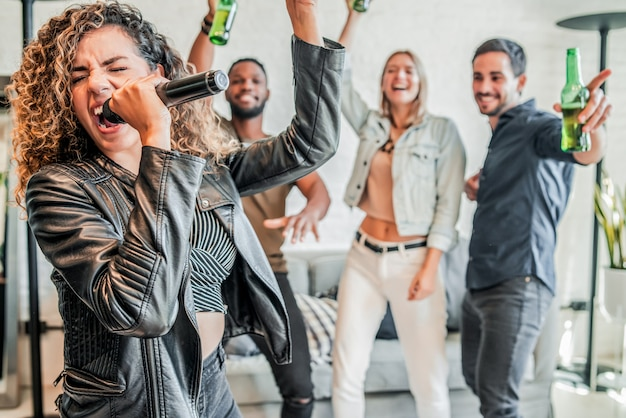 Gruppo di amici che si divertono insieme mentre giocano al karaoke a casa. concetto di amici.